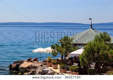 Two Loungers Under Sun Umbrella At The Beach Restaurant In Opatija, Croatia