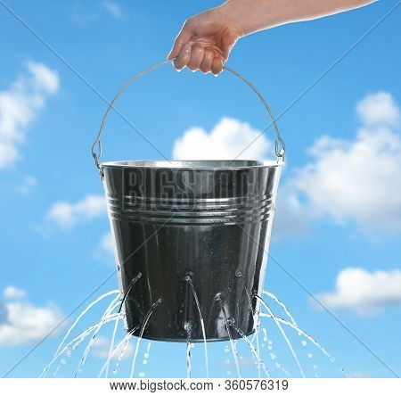 Woman Holding Leaky Bucket With Water Against Blue Sky, Closeup