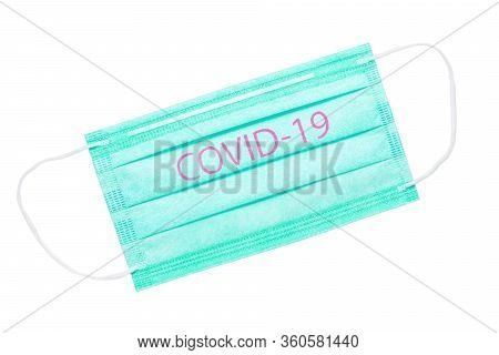 Green Medical Mask Isolated On White Background. Covid-19 Inscription On The Mask Symbolizing The Wo