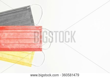 Three Medical Masks Of Black, Red And Yellow Are On The Left On A Light Background. Germany Pandemic