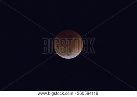 The Lunar Eclipse On The Evening Sky, Which The Moon Acquired A Reddish Hue Due To The Earth Shadow.