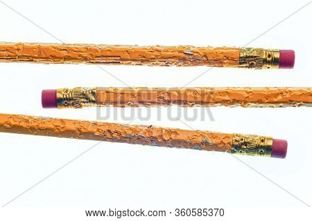 Horizontal Shot Of The Eraser End Of Three Chewed Pencils.  Two Are Coming From The Left Side And On