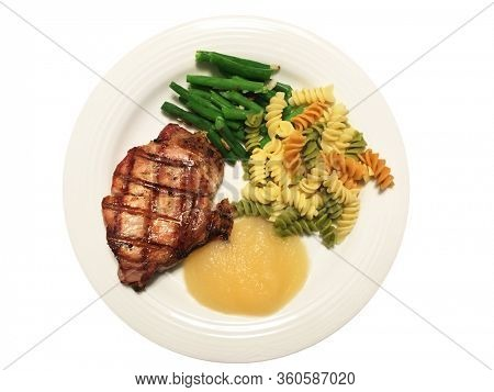 A grilled Pork Loin Chop on a plate with green beans and almond slices, tri-color rotini pasta and applesauce.