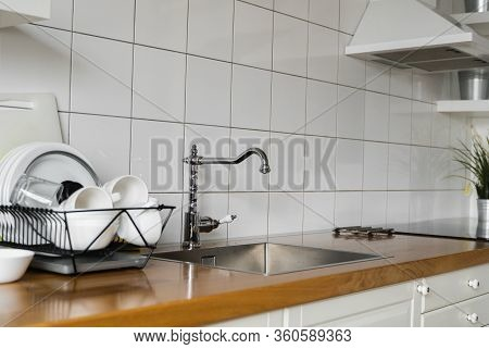 Kitchen Sink And Faucet. Stainless Kitchen Sink And Tap Water. The Interior Of The Modern Kitchen Ro
