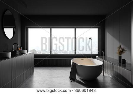 Interior Of Hotel Bathroom With Gray And Dark Wooden Walls, Concrete Floor, Comfortable White Bathtu