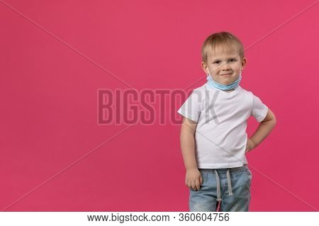 A Blond Boy Child Stands On A Bright Pink Background, Hand To Side And Looks Mockingly And Sarcastic