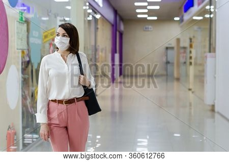 A Woman In A Medical Mask On Her Face Protecting From Coronavirus Is Walking Through The Store. Cons