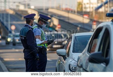 Bucharest, Romania - April 09, 2020: Police Officers Control Drivers In Traffic Checking Whether The