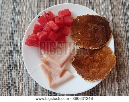 Having Watermelon, Ham And Hotcakes With Honey For Breakfast On A White Plate