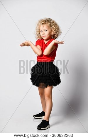 Frolic Curly Hair Blonde Kid Girl In Red T-shirt, Black Skirt And Sneakers Holds Hands Up With Open