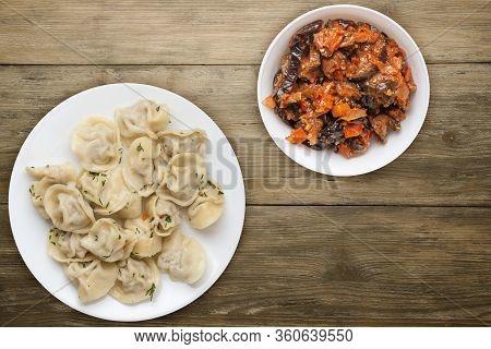 Dumplings On A White Plate On Wooden Background .boiled Dumplings With Salad.meat Dumplings Top View