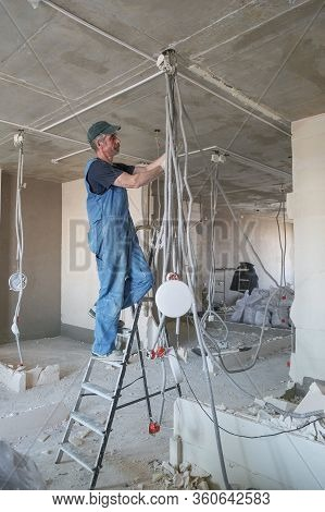 Worker Repairing The Electrical Wiring In A Newly Built House