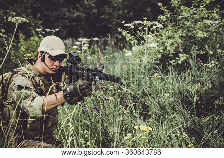 Focus On Gun. A Military Man Or Airsoft Player In A Camouflage Suit Sits In The Grass And Aims From