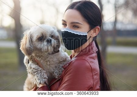 Outdoor Picture Of Delighted Lovely Young Female Wearing Antibacterial Mask To Protect From Coronavi