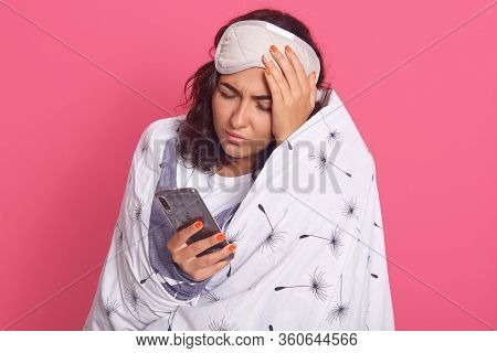 Indoor Shot Of Young Female With Hand On Head, Holding Smart Phone In Hand, Remembers Something, For