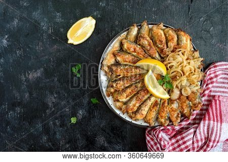 Fried Capelin, Sprats. Small Fried Fish On A Plate On A Black Background. Top View.