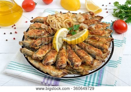 Fried Capelin, Sprats. Small Fried Fish On A Plate On A White Wooden Background.