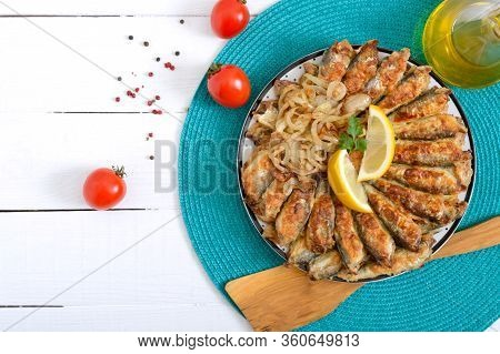 Fried Capelin, Sprats. Small Fried Fish On A Plate On A White Wooden Background. Top View.