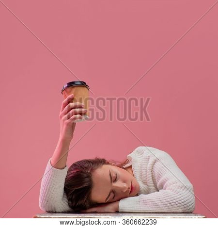 I Need More Coffee. Sleepy Student Girl Is Asleep And Pulls Her Hand With A Cup Of Coffee Up, Asking