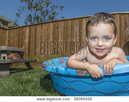Young Boy Looking Out Of His Paddling Pool