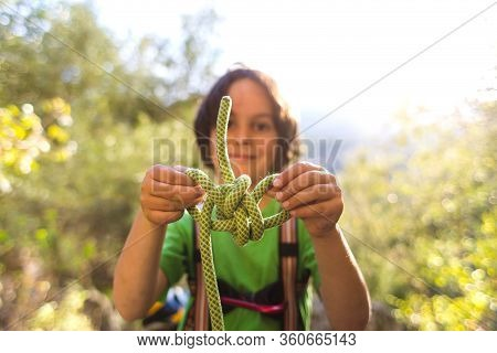 A Child Learns To Knit The Safety Knot From The Rope.