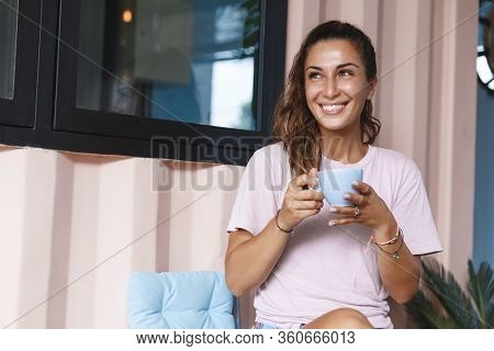 Sweet Home, Leisure And Happy Moment Concept. Smiling Woman Drinking Coffee, Hold Tea Cup And Look A