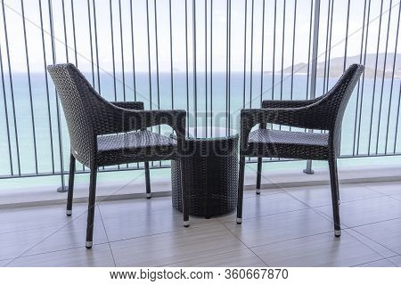 Two Rattan Chairs And A Table On The Balcony In High Hotel With Stunning Views Of The Sea And Tropic