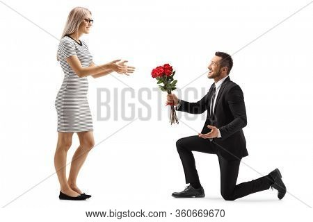 Young handsome man in a suit kneeling and giving a bunch of red roses to a woman isolated on white background