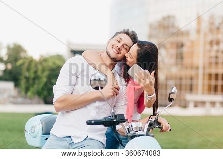 Blissful European Man Posing On Scooter While His Girlfriend Kissing Him. Adorable Young Woman With