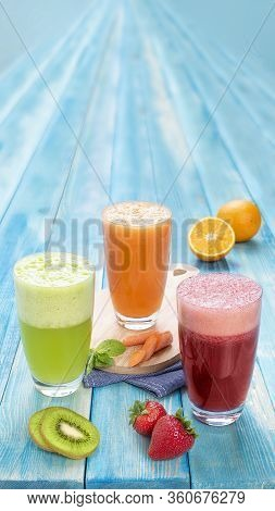Different Juices In One Group Picture Includes Kiwi Juice, Strawberry Juice, Orange Juice With Carro