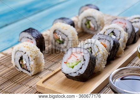 Sushi Rolls In A Row With Salmon, Rice And Cucumber On Blue Wood Background. White And Black Sushi,