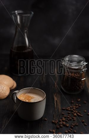 A Cup Of Black Americano Coffee Sits On A Black Table Next To Cookies And A Can Of Coffee Beans. A C