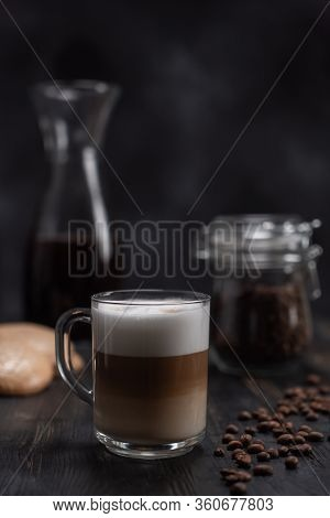 Transparent Cup Of Coffee Cappuccino Or Latte Is On The Black Table Next To Cookies And A Jar Of Cof