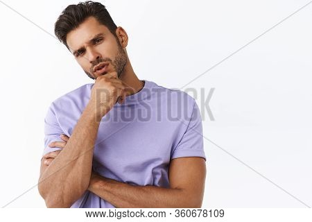 Close-up Shot Serious Bearded Attractive Man Thinking, Touching Chin And Tilt Head As Weighing What