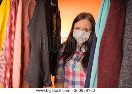 Close Up Of Young Sad Woman, Standing Between Clothes, Which Can Not Decide On Choice Of Clothing In