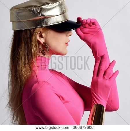 Young Beautiful Slim Blond Woman In Pink Longsleeve And Metallic Cap Standing Side Ways And Holding