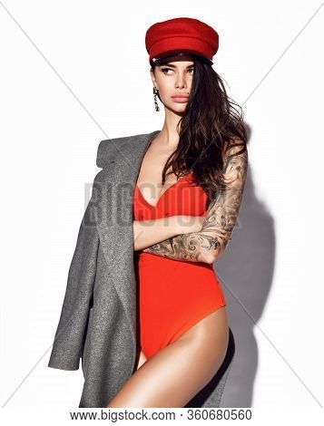 Young Beautiful Slim Brunette Woman With Tattooed Arm In Sexy Orange Swimsuit, Grey Coat And Red Cap