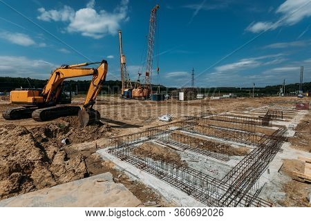 Yellow Excavator And The Foundation Of A Building At A Construction Site On A Sunny Day