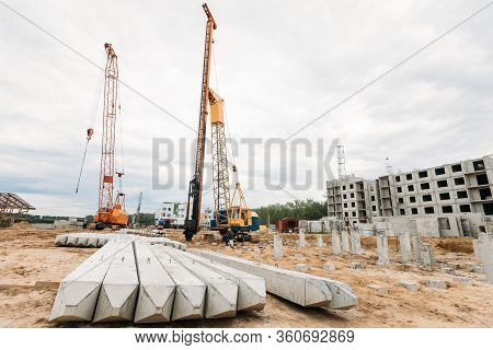 Construction Piles And Pile Driver During The Construction Of A Multi-storey Residential Building Au