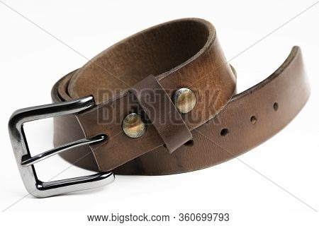 A Formal Studio Product Shot Of A Men's Used Brown Leather Belt With Patina Set On Plain White Backg