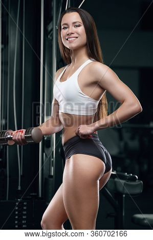 Fitness Woman Pumping Up Arm Muscles In The Gym