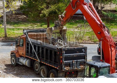 Excavator Picks Up Construction Waste For Loading Onto A Dump Truck