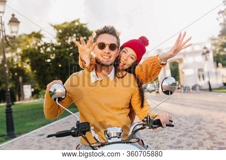 Lovely Girl In Cute Red Hat Waving Hands Enjoying Extreme Date With Boyfriend. Handsome Man In Dark