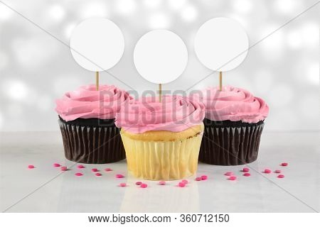Three Gourmet Cupcakes With Pink Frosting And Sprinkles Sitting Temptingly On A White Marble Backgro