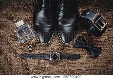 Black Shoes, Black Belt, Black Watch, Black Butterfly, Cufflinks And Perfume On A Brown Background W