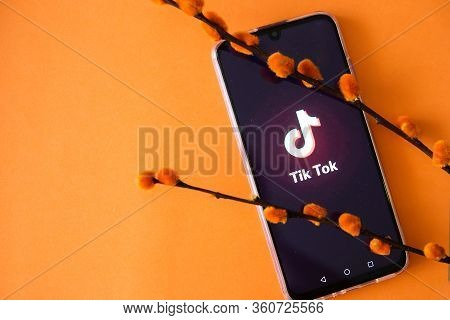 Tver, Russia-april 9, 2020 The Tik Tok Logo On The Smartphone Screen On An Orange Background Is Deco