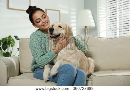 Young Woman And Her Golden Retriever On Sofa At Home. Adorable Pet