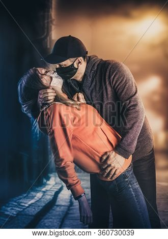 A Young Adult Man Kisses A Woman In Protective Medical Masks On A City Street At Night