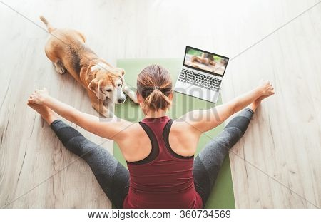 Top View At Fit Sporty Healthy Woman Sitting On Yoga Mat, Watching Online Yoga Class On Laptop Compu