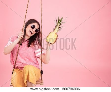 Young Woman On A Swing On A Pink Background.